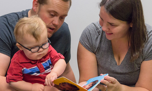 parents reading book with young child