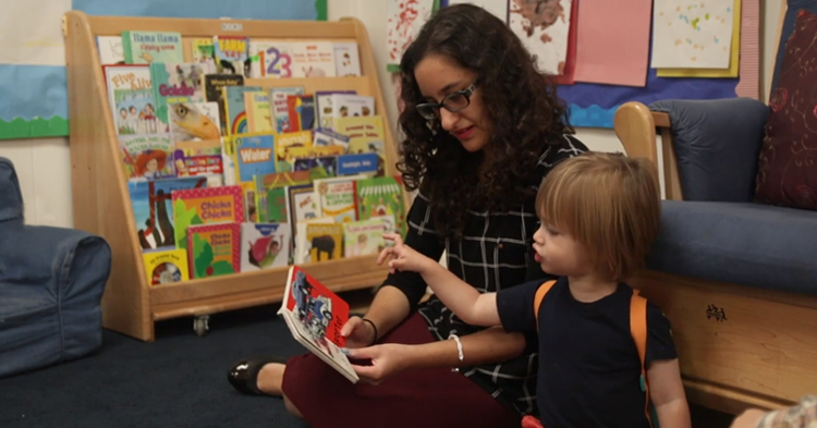 teacher reading with child at quality child care program