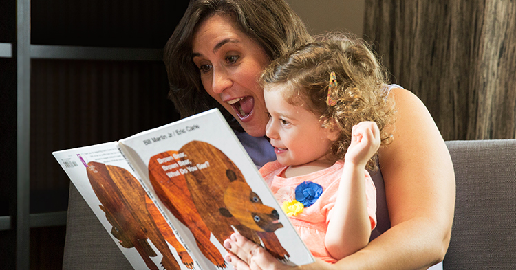 mom reads picture book to daughter