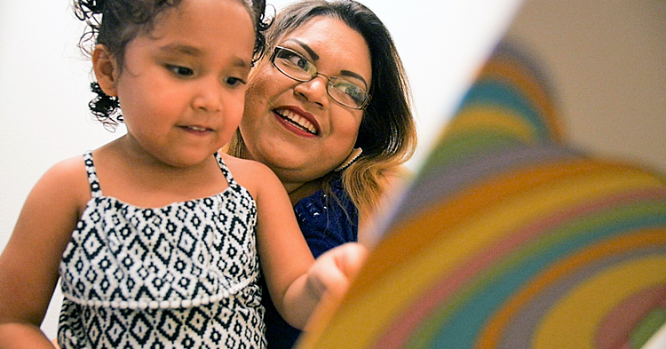 Mom reading with preschool daughter