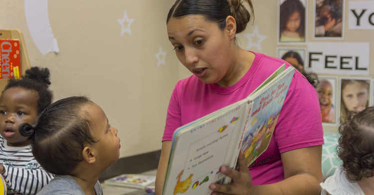 Early childhood educator reading to student