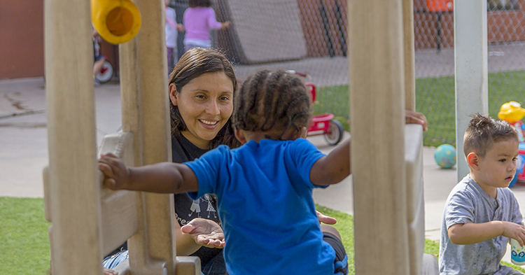 Child care worker with two toddler on playgrounds