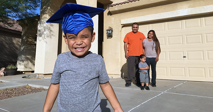 boy in graduation cap with family behind him