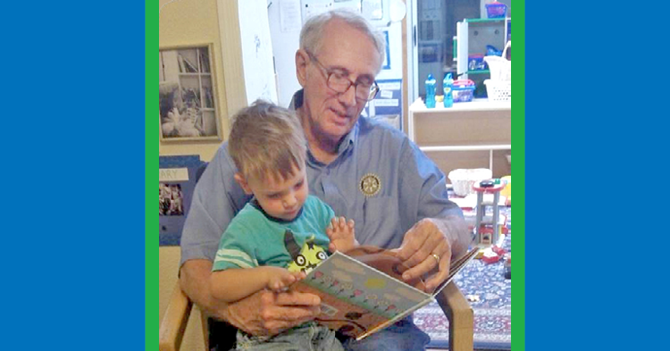 Elderly man reading with young boy