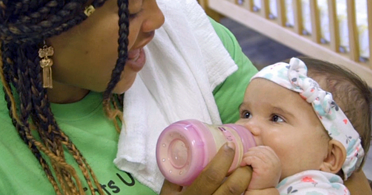 caregiver talks with baby while feeding