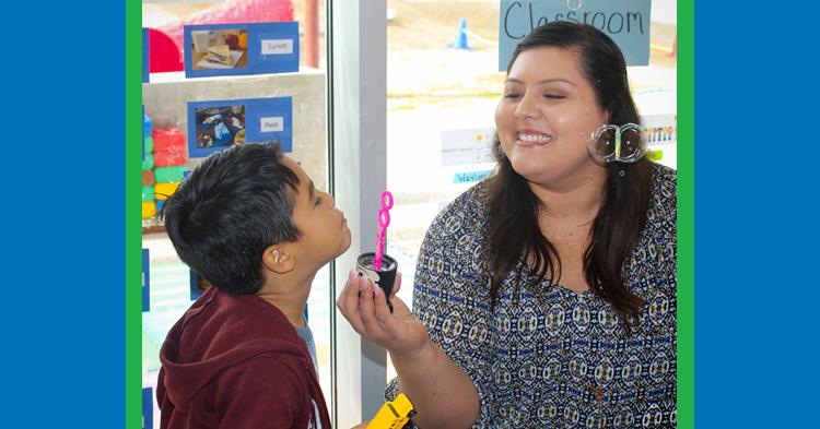 Little boy blowing bubbles with teacher.