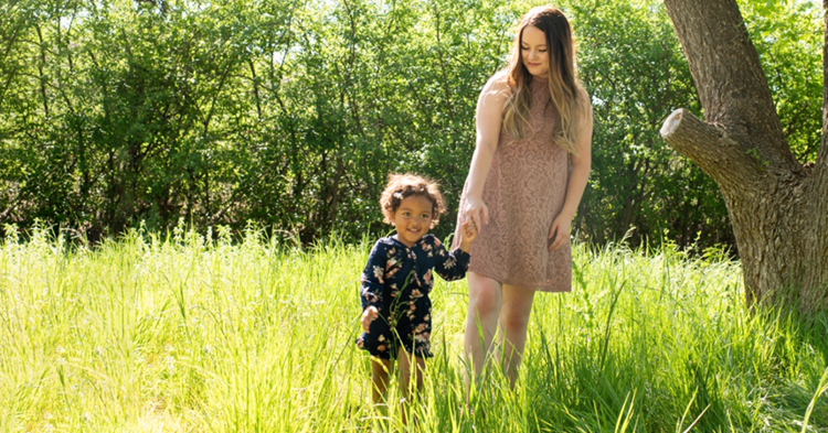mom and daughter walking through a grass field