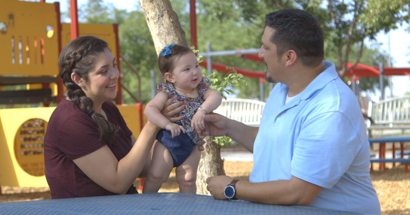 parents with baby in a park