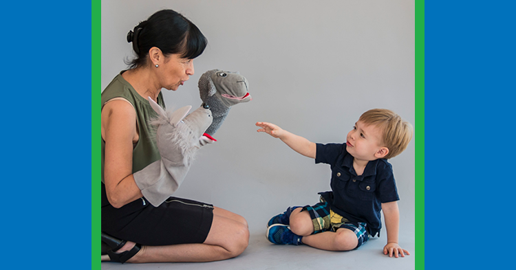 woman with puppet playing with toddler boy