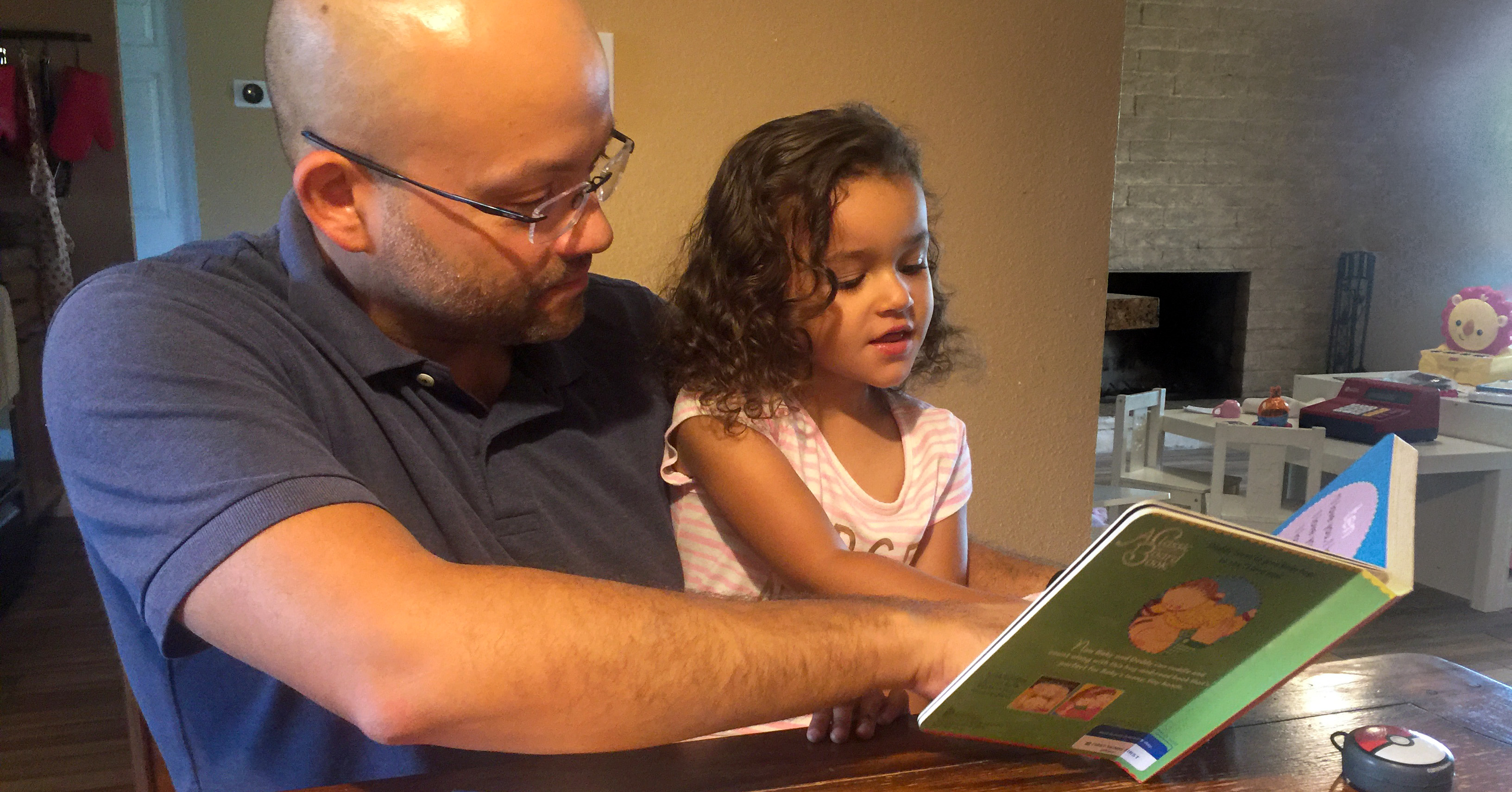 Dad reading book to young daugher