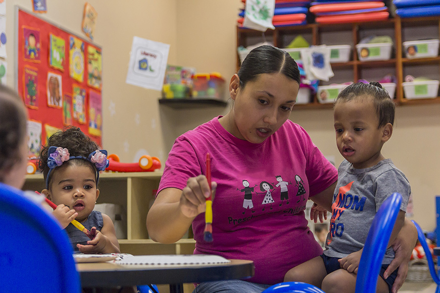 child care teacher works with young boy in a classroom.