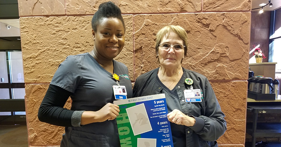 two nurses hold the FTF growth chart