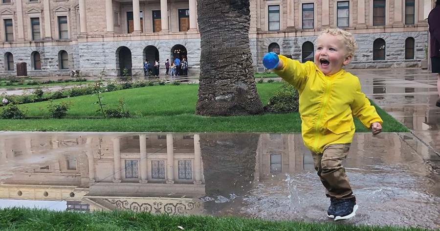 toddler in yellow rain jacket running