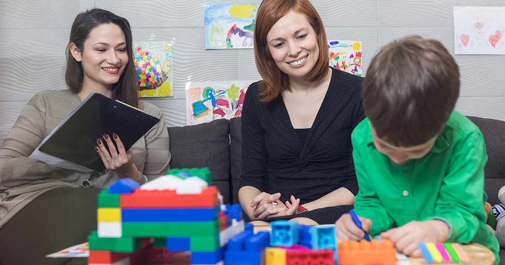 woman with clipboard and another woman sitting watching a small child play with blocks.