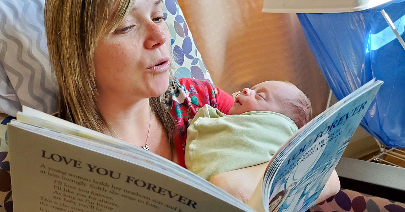 NICU nurse reading book to newborn