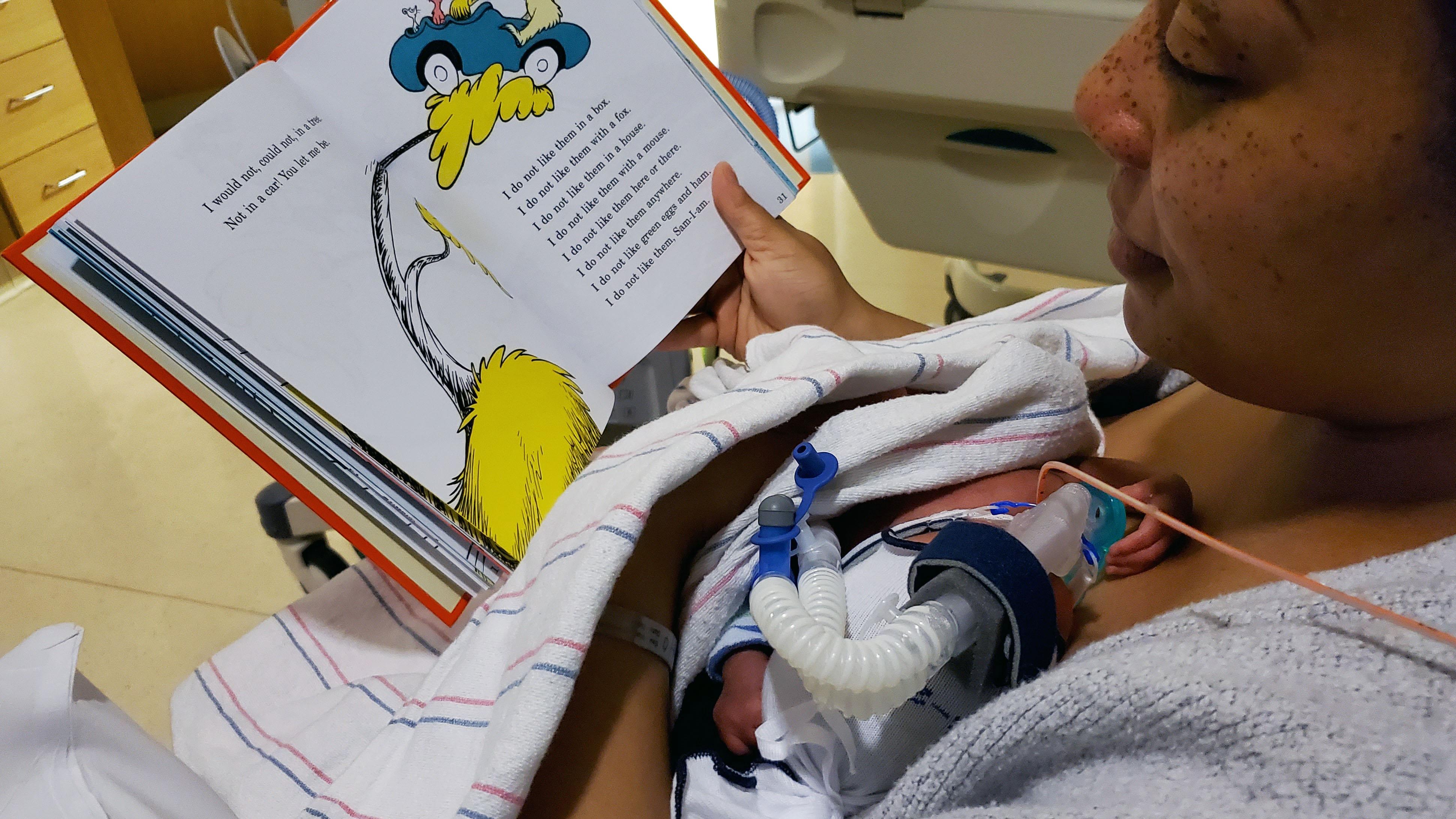 Parent reading book to newborn in NICU unit