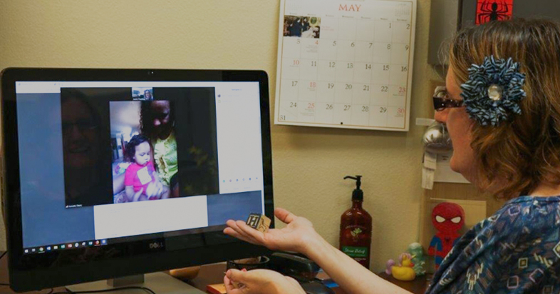 woman with headset, sitting in front of a computer, video chatting with a mom and her child