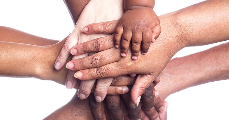 adult and children hands in unity