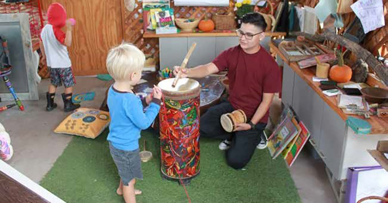 male pre-k teacher playing a drum with a young boy.g