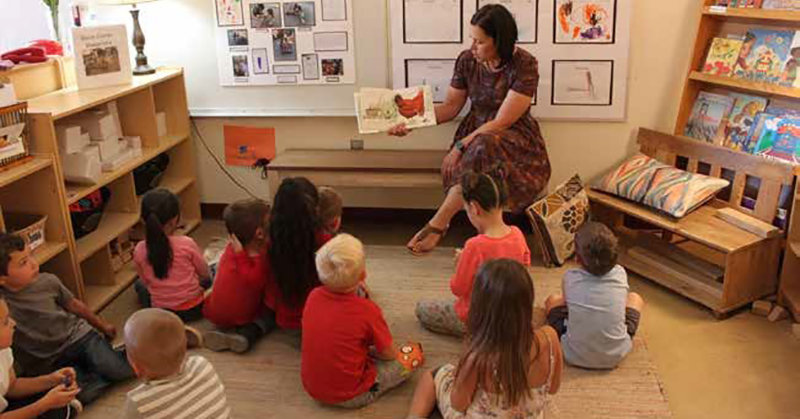 preschool teacher reading a book to a group of children