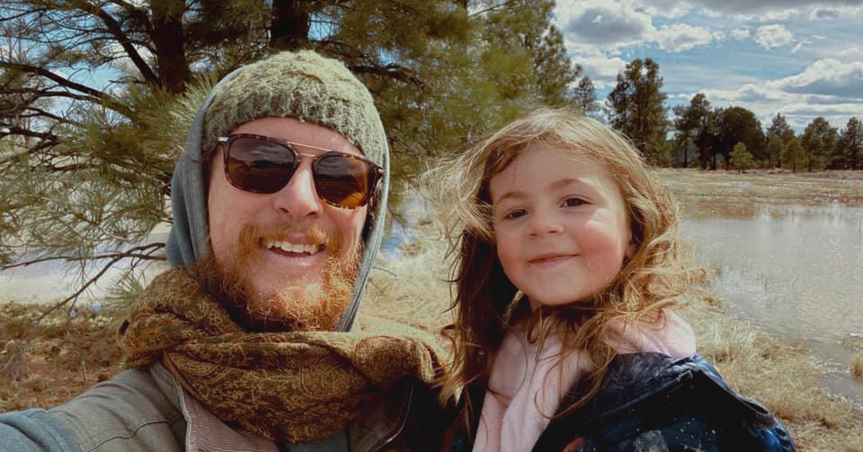 father in beanie wearing sunglasses with daughter who is smiling and wearing a denim jacket