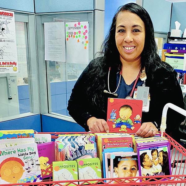 nurse standing next to a basket full of children's books