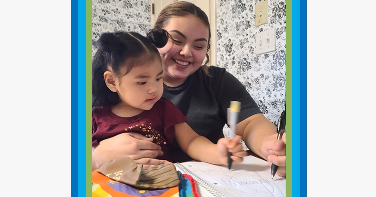 Mom with black tshirt holds her toddler daughter in her lap as they draw with markers.