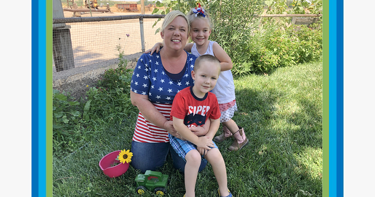 Mom kneeling, wearing a stars and stripes t-shirt, holding her son with a red tshirt and daughter standing next to her.