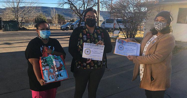 staff from Our Children Shelter stand outside holding a giftbag and award