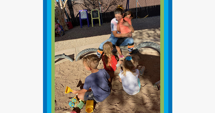 Woman in pink shirt cares for young children outside in a sandbox.