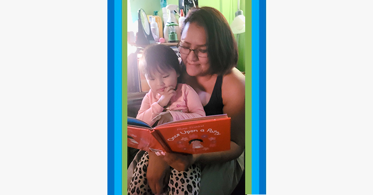 Mom reading a book to her toddler daughter