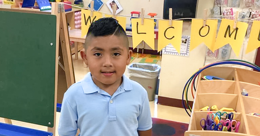 preschool boy with blue shirt standing in classroom