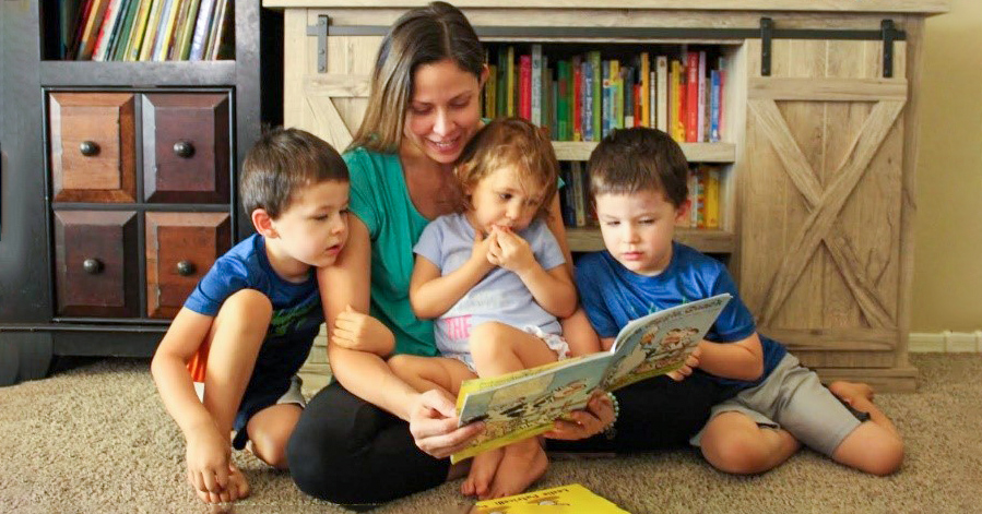 Mother reading to her children that are sitting next to her on the floor