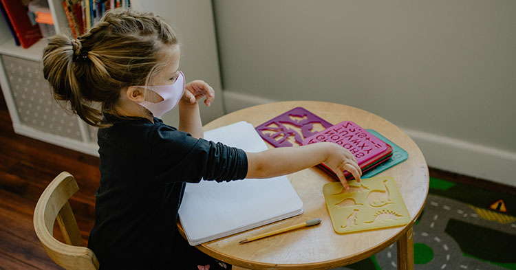preschooler drawing at a table with stencils
