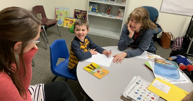 little boy at a table with woman doing a developmental screening.