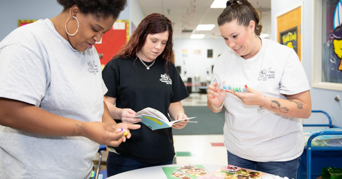 Three child care teachers training on early literacy, each holding children's books.