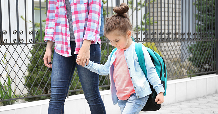 woman holding hand of young girl with backpack