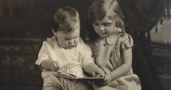 baby photo of Audrey Optiz reading to her baby brother.