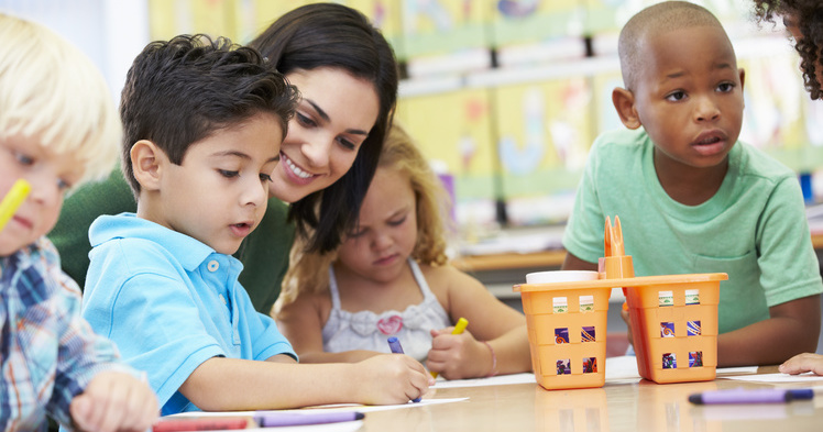 Teacher working with preschool aged boys and a girl in a classroom.
