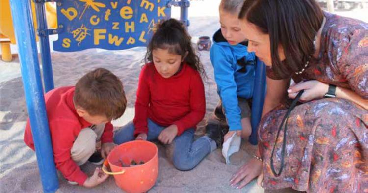 Woman kneeling in a sandbox with three preschool students.