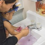 Teacher holding a young child over a sink helping to wash the child's hands.